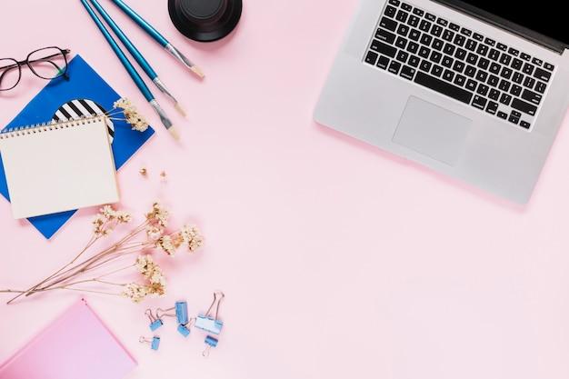 Ein offener laptop; blumen und briefpapier auf rosa hintergrund Kostenlose Fotos