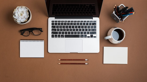 Ein offener laptop; mit kaffeetasse; papier; bleistifte; brillen und notizblock auf braunem papier hintergrund Kostenlose Fotos