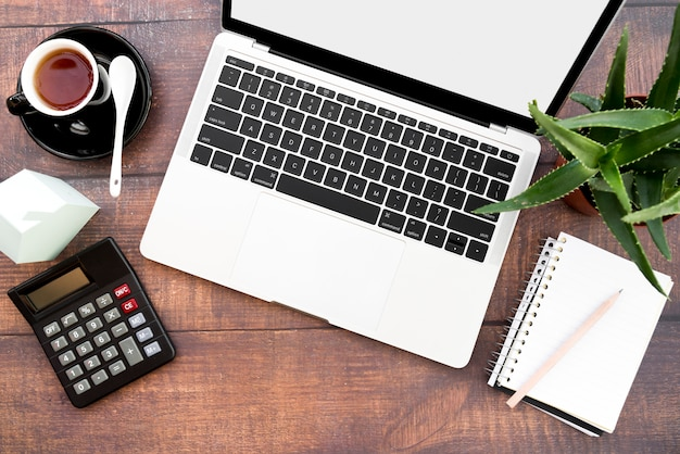 Ein offener laptop mit kaffeetasse; spiralblock; taschenrechner; papierhausmodell und aloe vera-pflanzen auf holztisch Kostenlose Fotos