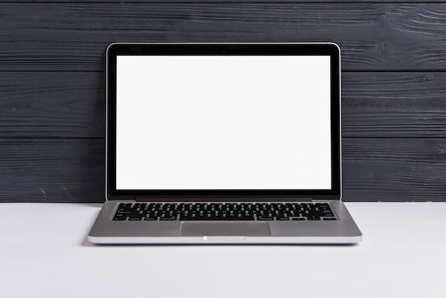 Ein offener laptop mit leerem weißem bildschirm auf weißem schreibtisch gegen schwarzen hölzernen hintergrund Kostenlose Fotos