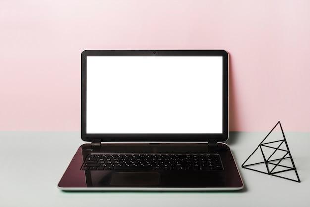 Ein offener laptop mit leerem weißem bildschirm gegen rosa hintergrund Kostenlose Fotos