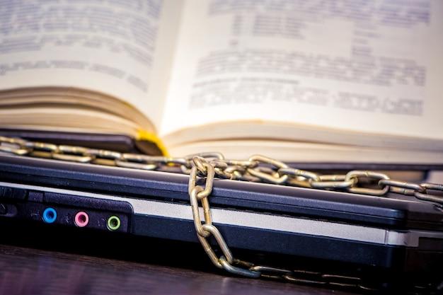 Ein offenes buch liegt auf einem laptop, der durch eine kette verbunden ist Premium Fotos