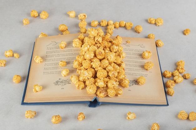 Ein offenes buch mit einem haufen karamellbeschichtetem popcorn auf marmor. Kostenlose Fotos