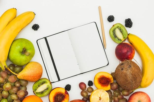 Ein offenes leeres notizbuch; bleistift und viele früchte auf weißem hintergrund Kostenlose Fotos