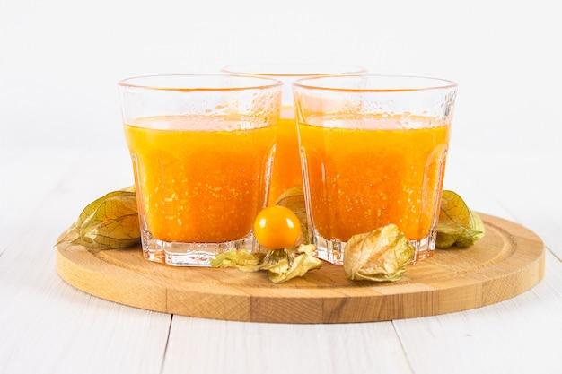 Ein orange smoothie gemacht vom physalis auf einem weißen holztisch. Premium Fotos