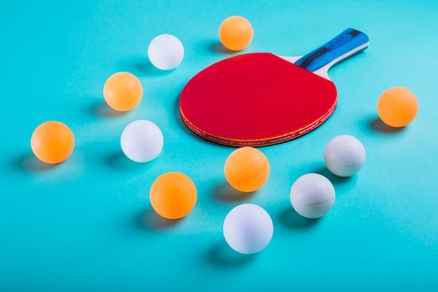 Ein orange und weiße bälle mit ping-pong-schläger auf blauem hintergrund Kostenlose Fotos