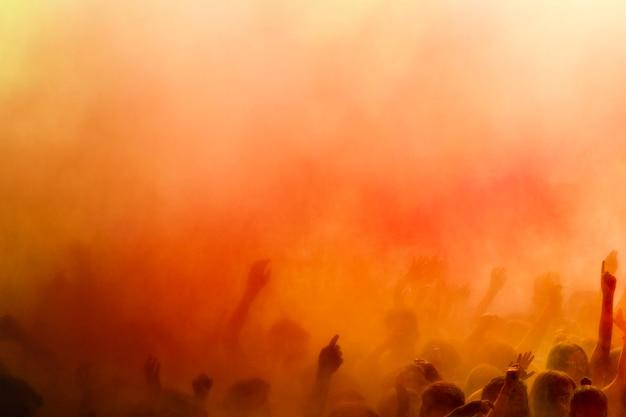 Ein orangefarbener holi überfärbt die menge Kostenlose Fotos