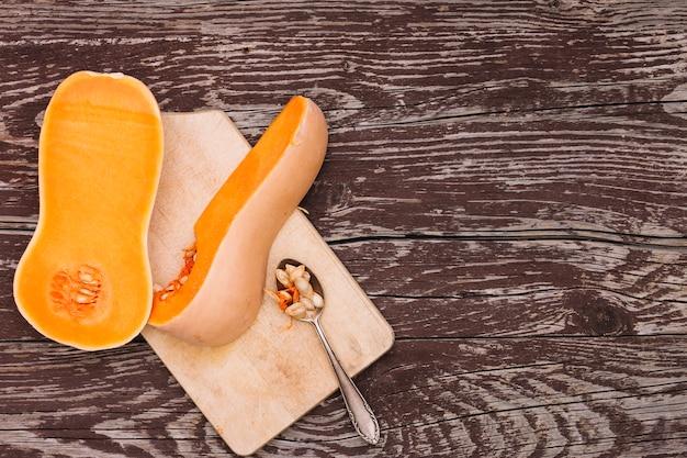 Ein organischer butternutkürbis und -samen auf löffel über dem hackenden brett gegen den hölzernen schreibtisch Kostenlose Fotos