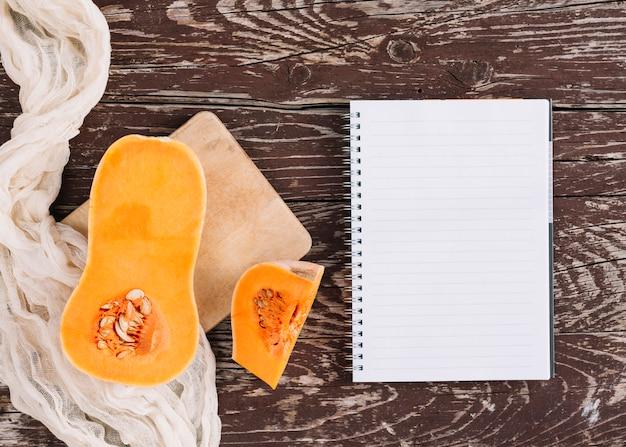 Ein organischer moschuskürbis auf stoff und schneidebrett mit gewundenem notizbuch auf hölzernem schreibtisch Kostenlose Fotos
