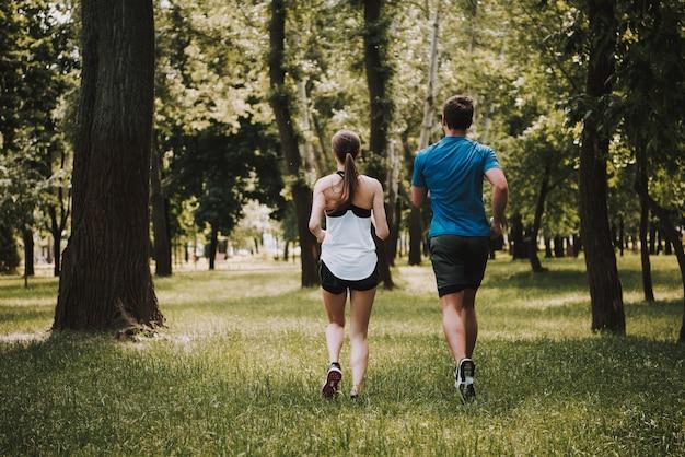 Ein paar athleten laufen zusammen im park. Premium Fotos