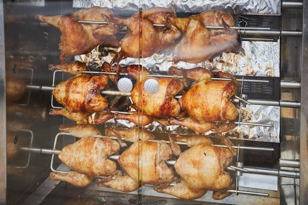 Ein paar ganze hühner werden auf einem elektrischen spieß gebraten Premium Fotos