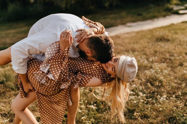 Ein paar liebhaber, die im park herumalbern. ehemann und ehefrau umarmen, küssen und haben spaß. Kostenlose Fotos