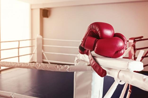 Ein paar rote boxhandschuhe hängt am ring Kostenlose Fotos