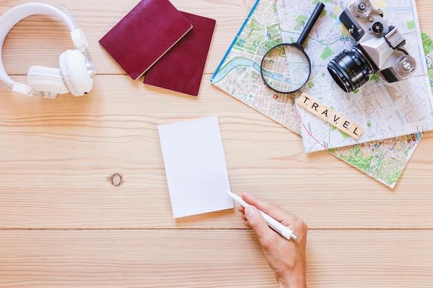 Ein personenschreiben auf papier mit reisenderzubehör auf hölzernem hintergrund Kostenlose Fotos