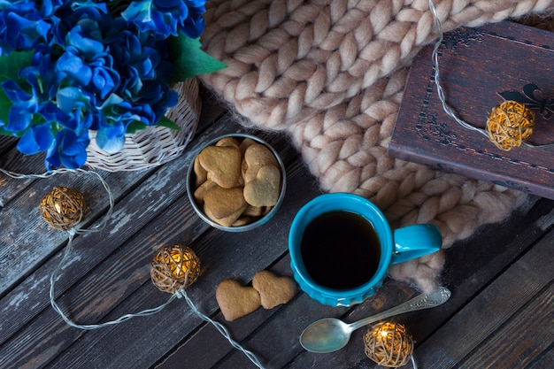 Ein plaid, ein buch, eine blaue teetasse, eine girlande und kekse Premium Fotos