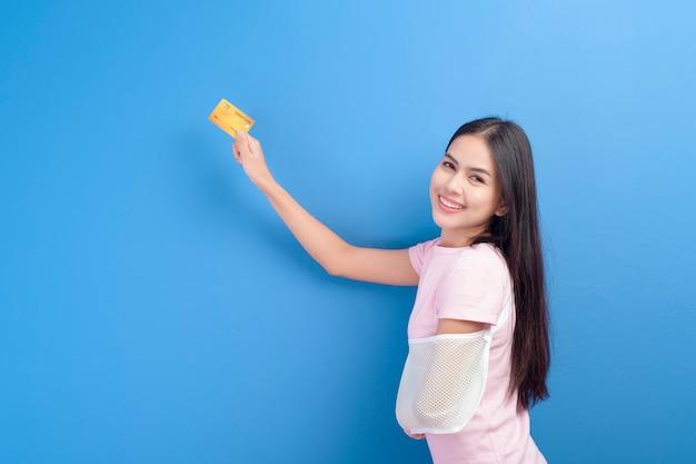 Ein porträt der jungen frau mit einem verletzten arm in einer schlinge, die eine kreditkarte oder eine krankenversicherungskarte über blauem hintergrund im studio-, versicherungs- und gesundheitskonzept hält Premium Fotos