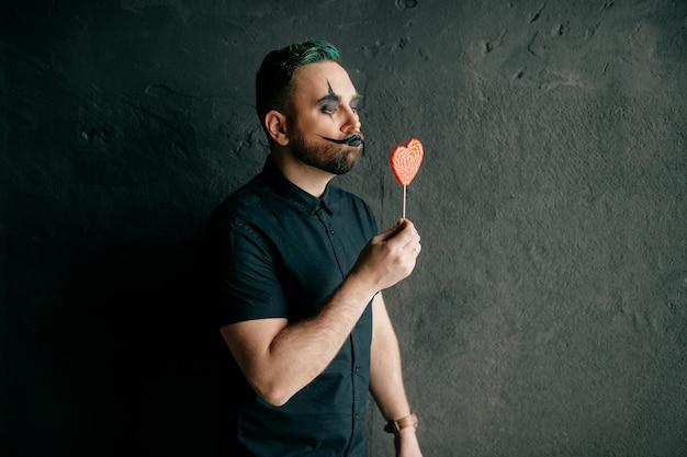 Ein porträt des gotischen schwarzen clowns, der mit lutscher aufwirft Premium Fotos