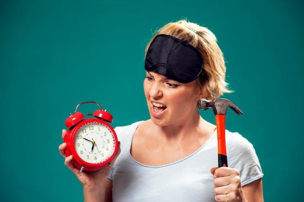 Ein porträt einer wütenden frau mit einer schlafmaske auf dem kopf, die hummer hält, wollte am morgen den roten wecker zerquetschen. Premium Fotos