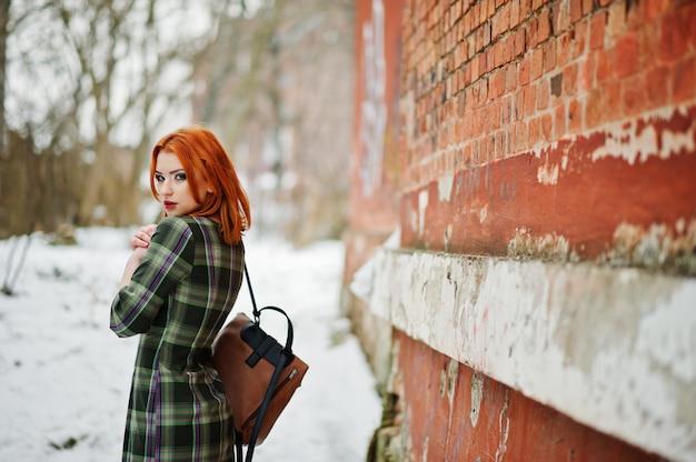 Ein porträt im freien einer jungen hübschen frau mit dem roten haar, das kariertes kleid mit den womany rucksäcken stehen auf der backsteinmauer am wintertag trägt. Premium Fotos