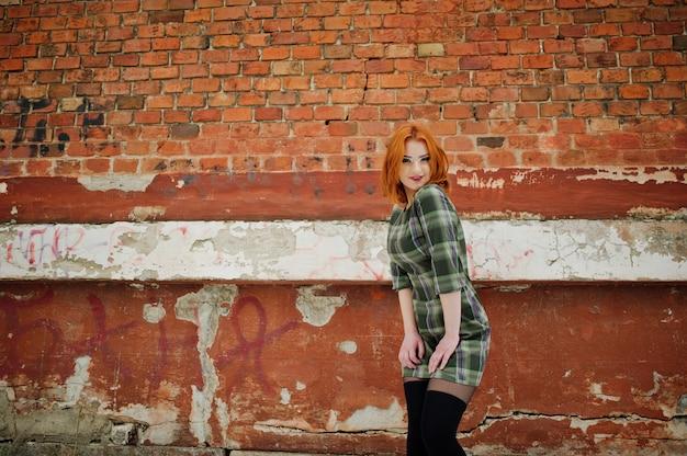 Ein porträt im freien einer jungen hübschen frau mit dem roten haar, welches das karierte kleid steht auf der backsteinmauer am wintertag trägt. Premium Fotos
