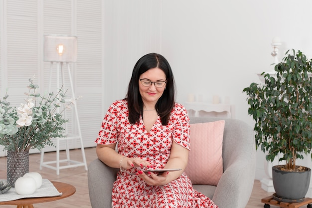Ein professioneller arzt psychologe mit brille sitzt in einem hellen büro mit einer tablette in seinen händen Premium Fotos