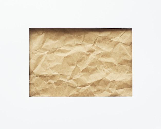 Ein rechteckiges loch in einem weißen blatt papier. zerknittertes bastelpapier im hintergrund. platz zum kopieren. Premium Fotos