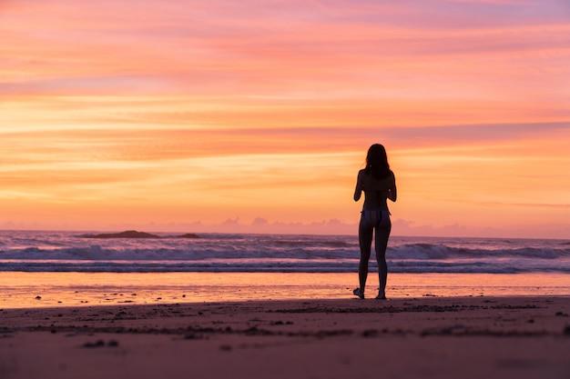 Ein reisemädchen, das am weißen sandstrand während der sonnenuntergangzeit sich entspannt Premium Fotos