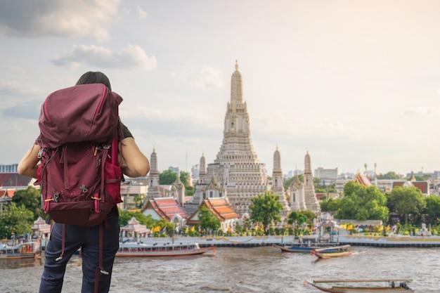 Ein reisender, der in wat arun ratchawararam ratchawaramahawihan temple in bangkok, thailand reist Premium Fotos