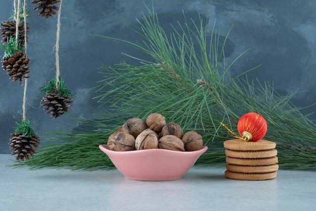Ein rosa teller voller walnüsse und süßer kekse auf marmorhintergrund. hochwertiges foto Kostenlose Fotos