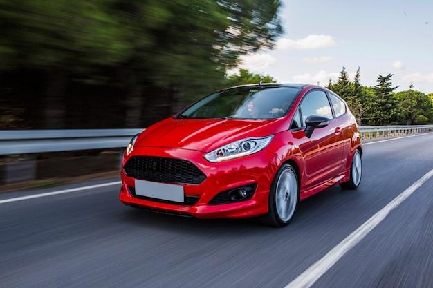 Ein rotes mini-coupé, das auf der autobahn fährt. Kostenlose Fotos