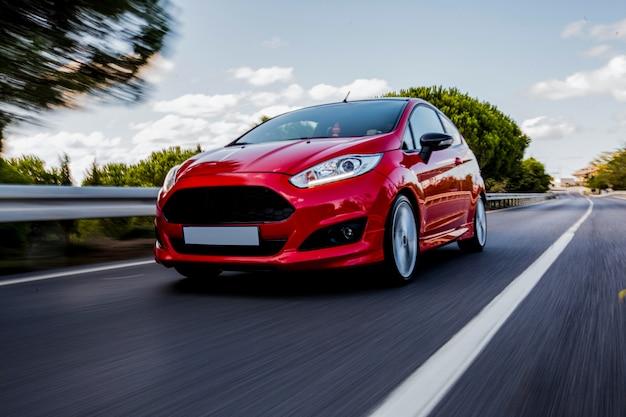 Ein rotes mini-coupé, das auf der autobahn mit hoher geschwindigkeit fährt. Kostenlose Fotos