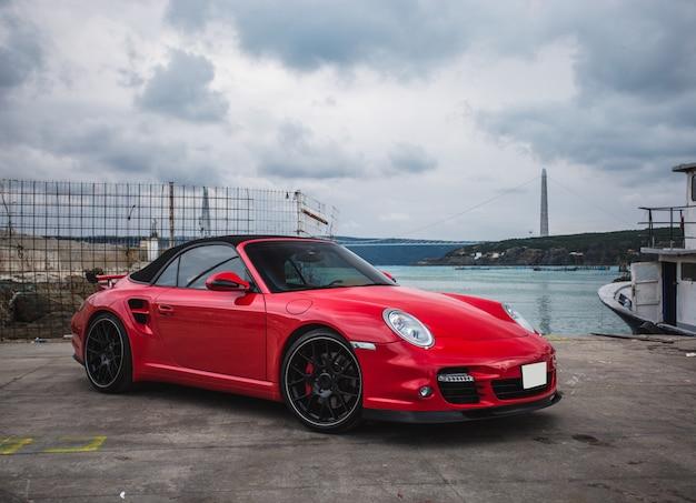 Ein rotes mini-coupé parkte im hafen. vorderansicht. ein schiff am meer. Kostenlose Fotos