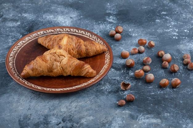 Ein runder teller mit frischen croissants und gesunden macadamianüssen. Kostenlose Fotos
