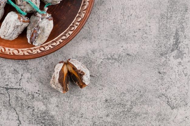 Ein runder teller voller getrockneter kaki-früchte auf einem steintisch. Kostenlose Fotos