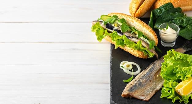 Ein sandwich aus heringsfilet mit zwiebeln, gurken und salat auf einem steinbrett machen Kostenlose Fotos