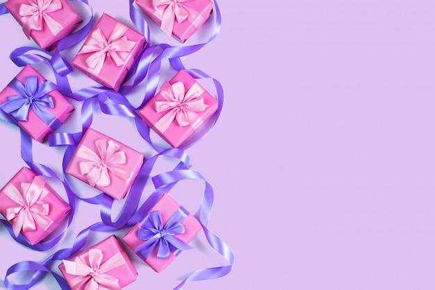 Ein satz geschenke für eine neugeborene rosafarbene farbe auf einem violetten hintergrund Premium Fotos