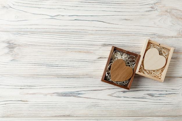 Ein satz von zwei dekorativen hölzernen herzen aus holz hintergrund mit kopie raum. ein geschenk zum valentinstag in einer holzkiste hautnah. liebesgeschichte konzept. Premium Fotos