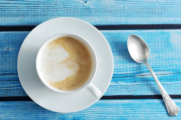 Ein schaumiger kaffee mit cappuccino in einem weißen becher auf einem blauen hölzernen hintergrund Premium Fotos