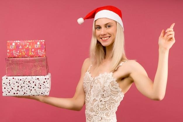 Ein schöner athletischer transgender-mann in einem neujahrshut und einem weißen kleid, halten in den händen geschenke Premium Fotos
