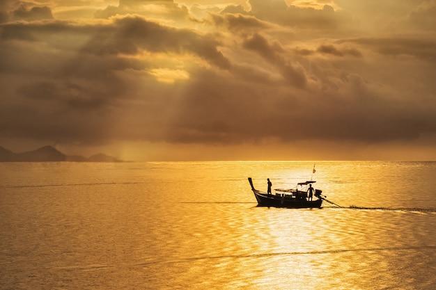 Ein schöner goldener sonnenuntergang auf dem meer, asiatischer fischer auf hölzernem boot mit sonnenuntergangzeit Premium Fotos