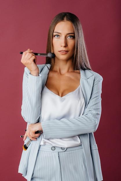 Ein schöner junger maskenbildner posiert in einem anzug mit quasten auf dem hintergrund im studio. bilden Premium Fotos