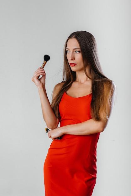 Ein schöner junger maskenbildner wirft mit quasten auf einem weißen hintergrund im studio auf. bilden Premium Fotos