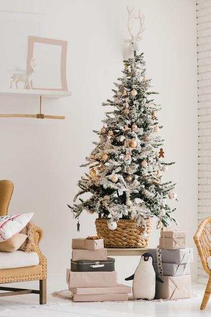Ein schöner weihnachtsbaum mit künstlichem schnee steht im wohnzimmer in den beige und hellen farben Premium Fotos