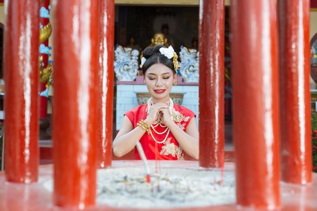 Ein schönes asiatisches mädchen, das eine rote anbetung trägt Kostenlose Fotos
