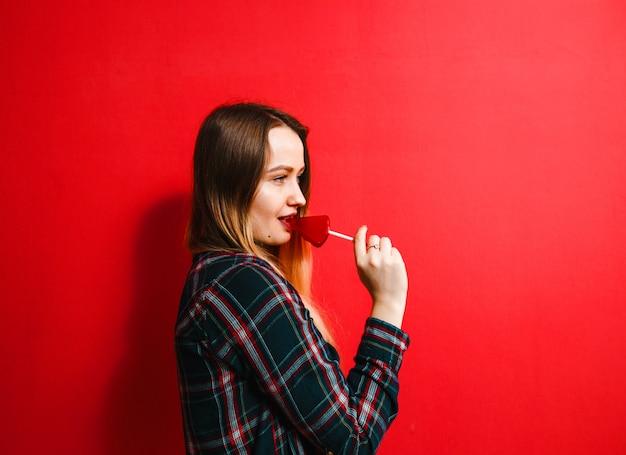 Ein schönes brunettemädchen mit einer süßigkeit in ihrer hand, die spaß auf einem roten hintergrund hat. Premium Fotos