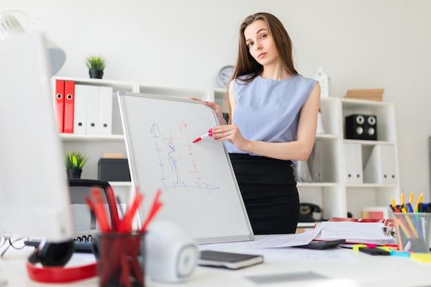 Ein schönes junges mädchen in einem büro steht in der nähe eines tisches und erklärt auf einer magnetischen tafel einen kies. Premium Fotos