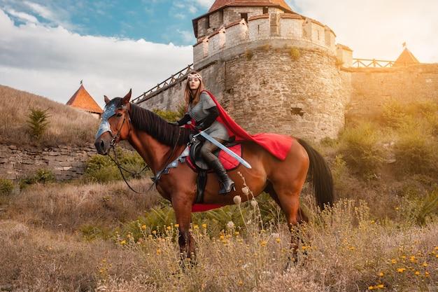 Ein schönes mädchen im kostüm der kriegerkönigin. eine frau zu pferd mit einem schwert in der hand. Premium Fotos