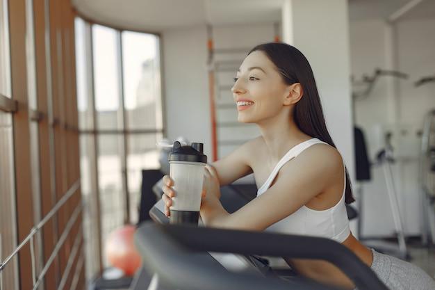 Ein schönes mädchen in einem fitnessstudio auf einer rennstrecke Kostenlose Fotos
