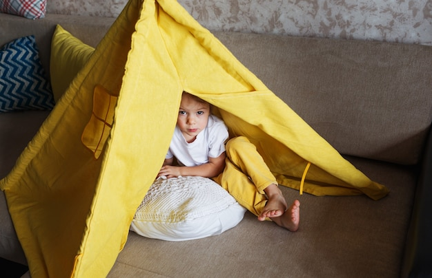 Ein schönes mädchen in gelben hosen und einem weißen t-shirt spielt mit der innenseite eines tipis zu hause auf der couch. heimspiele für kinder Premium Fotos