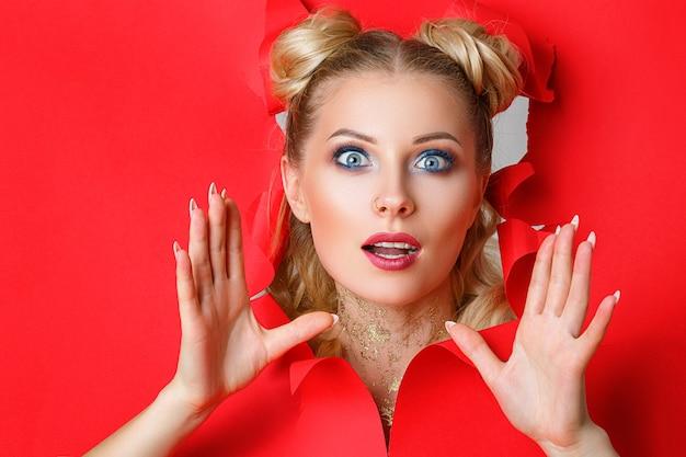 Ein schönes mädchen klettert aus einem loch im roten papier heraus Premium Fotos